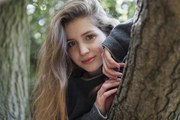 Portrait of smiling Caucasian teenage girl leaning on tree