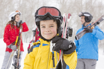 Portrait of smiling Caucasian boy carrying skis