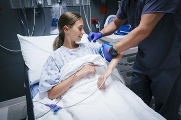 Nurse is measuring blood pressure of girl in hospital