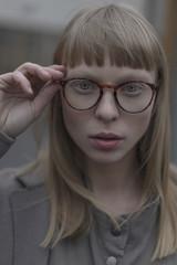 Portrait of serious Caucasian woman holding eyeglasses