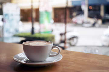Closeup image of a white cup of latte coffee on wooden table in cafe with blur background