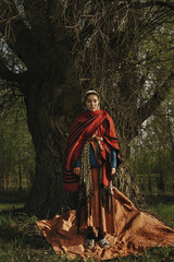 Caucasian woman wearing traditional clothing standing near tree