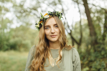 Middle Eastern woman wearing flower crown in woods