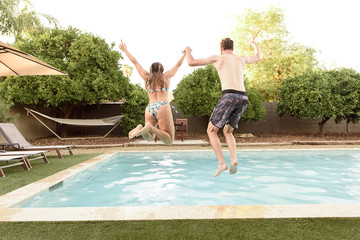 Caucasian couple holding hands jumping into swimming pool