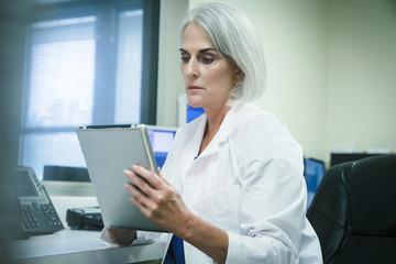 Serious Caucasian doctor using digital tablet