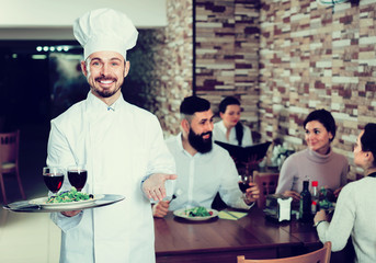 happy male cook showing country restaurant