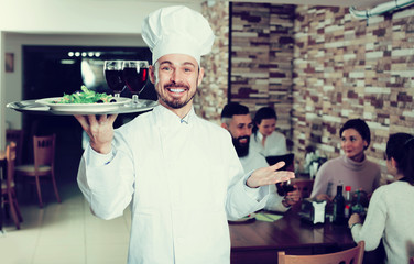 Happy male chef demonstrating country restaurant
