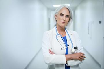 Portrait of smiling female doctor standing in hospital corridor