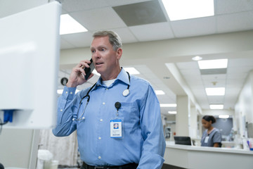 Doctor using computer and talking on cell phone