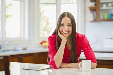 Portrait of smiling Hispanic woman in domestic kitchen