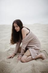 Caucasian woman kneeling in sand