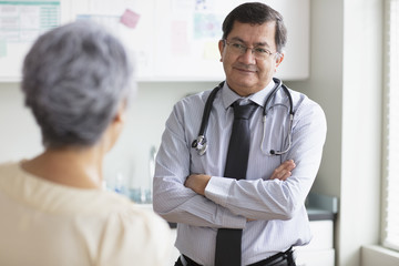 Hispanic doctor with arms crossed listening to patient