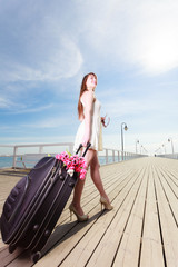 Young woman walking with suitcase on wheels