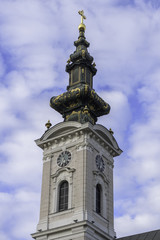 Church tower of Saint George's Cathedral in city of Novi Sad, Serbia against blue sky and clouds