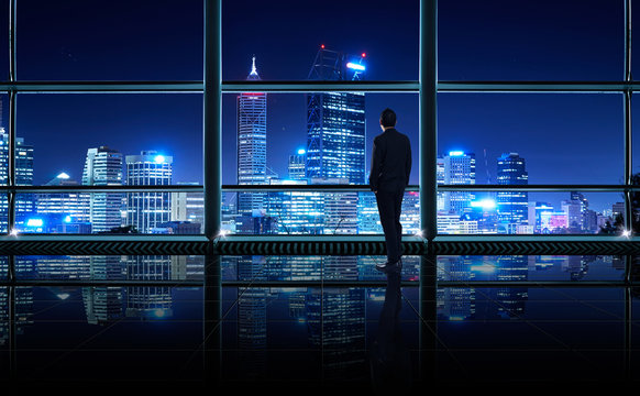 Back view of thoughtful businessman looking out of big office window at office ,planning future project concept,night scene .