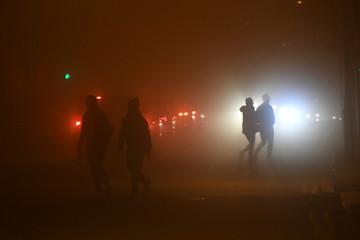 People walk across a road during heavy fog in Dublin