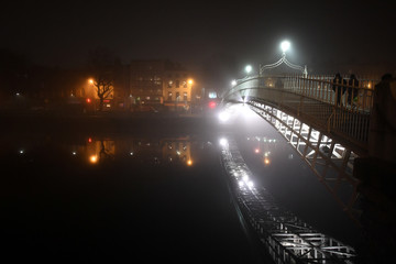 People cross the Ha'penny bridge during heavy fog in Dublin