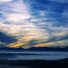 Mountain range with visible silhouettes through the morning colorful fog.
