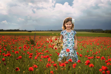 Among the spring field / Beautiful little girl on the background of a poppy field, Bulgaria