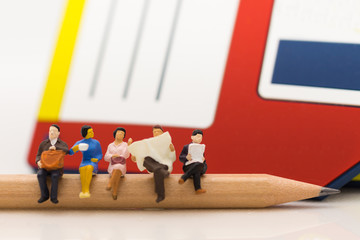 Miniature people: Business team sitting on the pencil with floppy disk drive for background, reading news paper, using as background business, education concept.