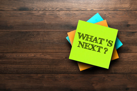 What's next, the phrase is written on multi-colored stickers, on a brown wooden background. Business concept, strategy, plan, planning.