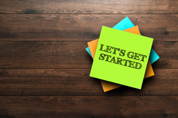 Let's Get Started, the phrase is written on multi-colored stickers, on a brown wooden background. Business concept, strategy, plan, planning.