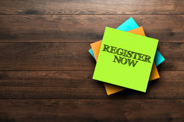 Register Now, the phrase is written on multi-colored stickers, on a brown wooden background. Business concept, strategy, plan, planning.