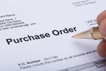 Person Hand Filling A Purchase Order Form