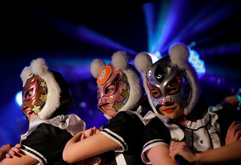 "Members of Japan's idol group ""Virtual Currency Girls"" wearing cryptocurrency-themed masks perform in their debut stage in Tokyo"