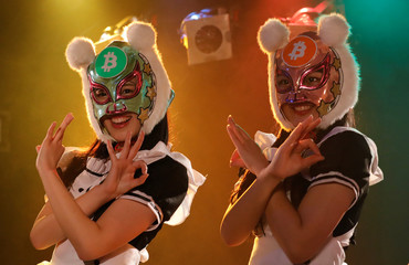 "Members of Japan's idol group ""Virtual Currency Girls"" wearing cryptocurrency-themed masks pose after performing in their debut stage event in Tokyo"