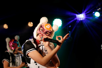"Members of Japan's idol group ""Virtual Currency Girls"" wearing cryptocurrency-themed masks perform in their debut stage event in Tokyo"