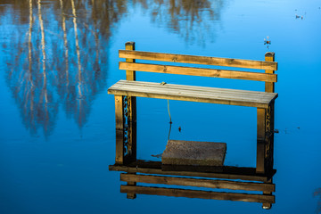 Frost covered wooden bench standing in the water on flooded riverbank. The river Braknean in southern Sweden.