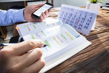 Fototapete - Businessperson's Hand Planning Schedule In Diary