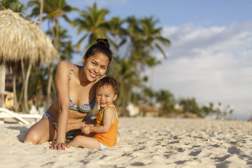 Mother and her baby are on a beach