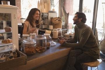 Smiling waitress talking to customer
