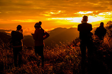 Photo silhouette and travel.They are stading on mountains and see the sunset / sunup. A man take photo and woman play mobile phone. they are fun .