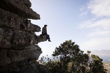 Hiker sitting on rock cliff