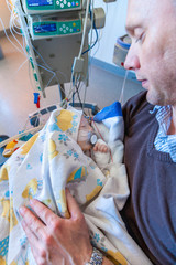 A father sitting on a chair in a intensive care unit holding his sick infant boy wrapped in a blanket surrounded by medical equipment. Vertical view.