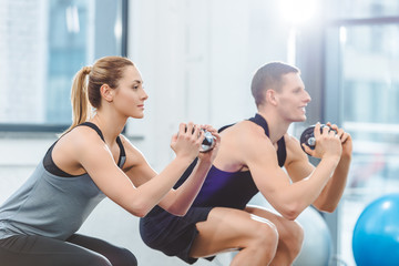 sporty young couple holding dumbbells and doing squat exercise in fitness studio