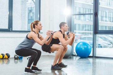 sporty young couple holding dumbbells and doing squat exercise in gym