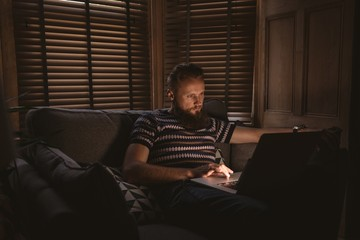 Man in dark room sitting on sofa using his laptop