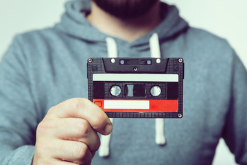 Hand holding  cassette tape. Used cassette tape. Audio cassette. Vintage audio cassette tap in the hand. Old cassette tape audio isolated on white.