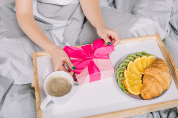 cropped image of girl opening present box in morning