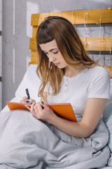 girl writing something to notebook in bed in morning