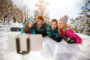 family enjoying winter vacations in mountains and making selfie