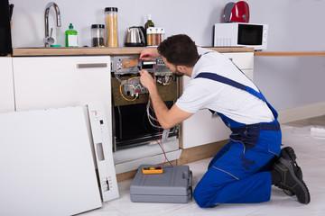 Male Technician Examining Dishwasher