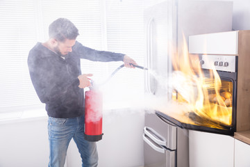 Man Using Fire Extinguisher To Stop Fire Coming From Oven Wall mural