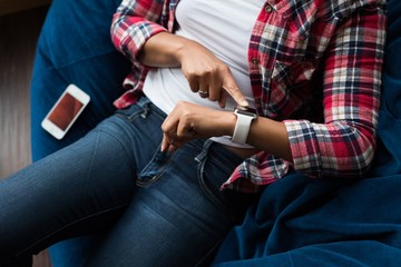 Female executive sitting on arm chair and using smartwatch