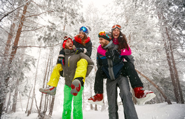 Group of friends having fun in forest on the snow