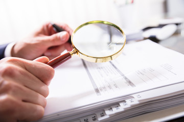 Businessperson Checking Bill With Magnifying Glass